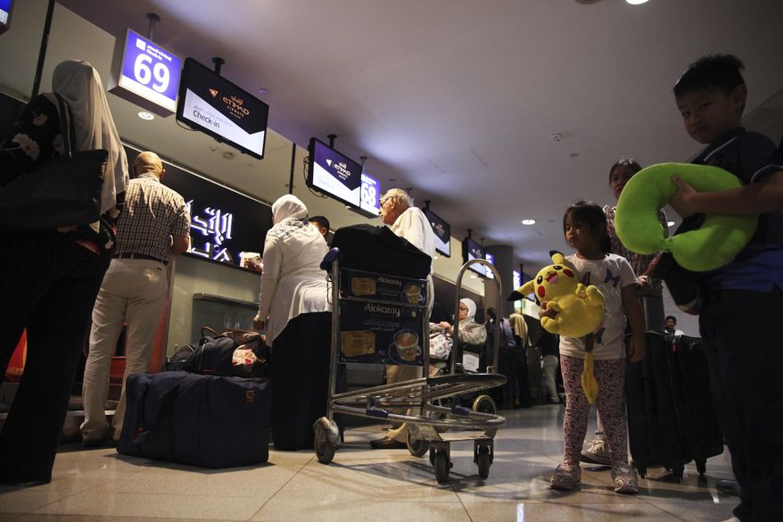 Passengers check into a flight at Abu Dhabi International Airport in Abu Dhabi, United Arab Emirates, Tuesday, July 4, 2017. Abu Dhabi's airport is the first among Mideast airports targeted by a U.S. ban on laptops in airplane cabins to be exempt from the list. (AP Photo/Jon Gambrell)