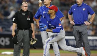 From left, home plate umpire Jerry Meals, Toronto Blue Jays manager John Gibbons and Blue Jays trainer, Mike Frostad, right, watch as Toronto Blue Jays starting pitcher Marcus Stroman (6) throws under supervision during the fifth inning of a baseball game against the New York Yankees in New York, Monday, July 3, 2017. (AP Photo/Kathy Willens)