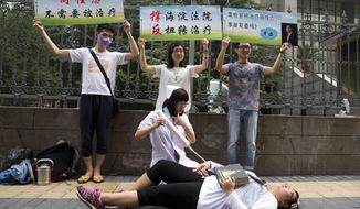 FILE - In this July 31, 2014 file photo, gay rights campaigners act out electric shock treatment to protest outside a court when the first court case in China involving so-called conversion therapy is held in Beijing, China. A gay man in central China has successfully sued a mental hospital over forced conversion therapy on June 26, 2017, in what activists are hailing as the first such victory in the country where the LGBT rights movement is gradually emerging form the fringes. (AP Photo/Ng Han Guan, File)