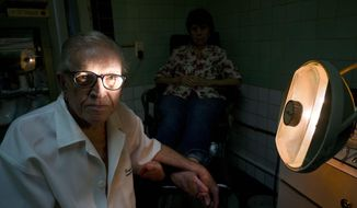 In this June. 8, 2017 photo, podiatrist Serafin Barca poses for a photo with a patient in his clinic in Havana, Cuba. The 80-year-old podiatrist is one of the last private medical workers in communist Cuba, which prides itself on its free, universal state health care. (AP Photo/Ramon Espinosa)