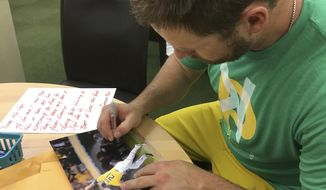 In this June 15, 2017, photo, then-Oakland Athletics catcher Stephen Vogt autographs fan mail before a baseball game between the Athletics and the New York Yankees in Oakland, Calif. Vogt recently got caught up on two years' worth of fan mail; he remembers being that child collecting autographs at every chance. (AP Photo/Janie McCauley)