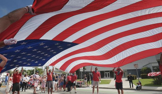 Participants carry an American flag during the 4th of July parade in Santa Monica, Calif. on Tuesday, July 4, 2017. Decked out in red, white and blue, Californians waved flags and sang patriotic songs at Independence Day parades across the state. (AP Photo/Richard Vogel)