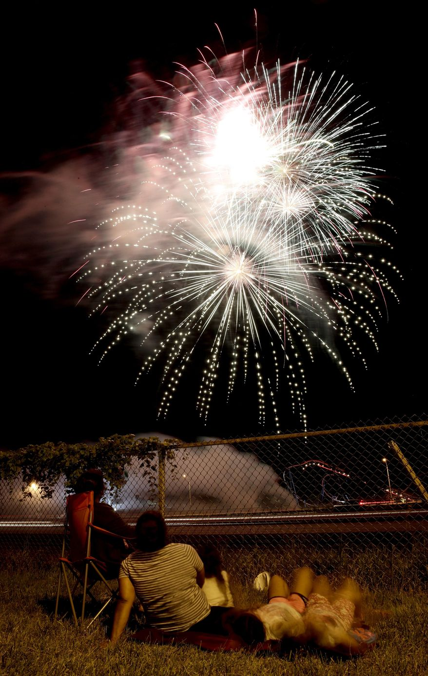 People watch a fireworks display for Independence Day at Worlds of Fun amusement park Monday, July 3, 2017, in Kansas City, Mo. (AP Photo/Charlie Riedel)