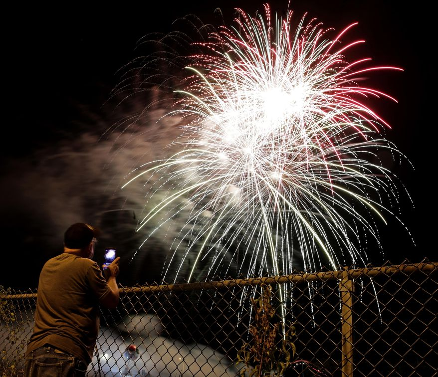 A man watches a fireworks display for Independence Day at Worlds of Fun amusement park Monday, July 3, 2017, in Kansas City, Mo. (AP Photo/Charlie Riedel)