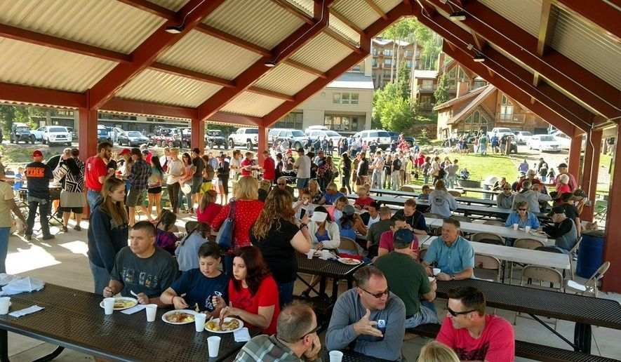 In a photo provided by Bret Howser, people attend a pancake breakfast in Brian Head, Utah on Tuesday, July 4, 2017, that volunteers and residents put on for local firefighters who've been fighting a wildfire that forced the evacuation of the town for nearly two weeks.  (Bret Howser via AP)