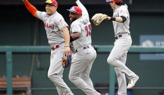 Miami Marlins' Giancarlo Stanton, left, celebrates with teammates Marcell Ozuna and Christian Yelich, right, following a baseball game against the St. Louis Cardinals, Tuesday, July 4, 2017, in St. Louis. The Marlins won 5-2. (AP Photo/Jeff Roberson)