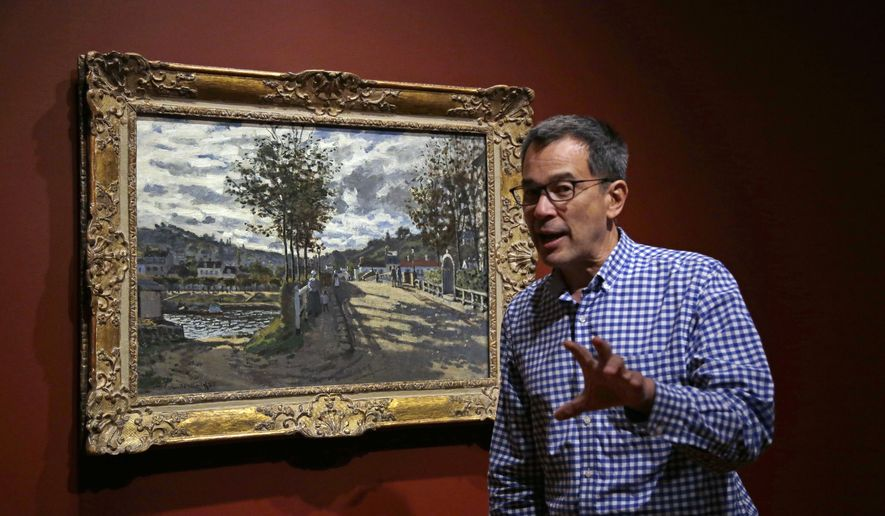 """In this June 29, 2017 photo, Director of Currier Museum of Art, Alan Chong, speaks about Claude Monet's 1869 painting, """"The Bridge at Bougival"""" in the galley in Manchester, N.H. The beloved Monet painting along with three of his others show the artist's evolution in """"Monet: Pathways to Impressionism"""" which opened on July 1. (AP Photo/Elise Amendola)"""