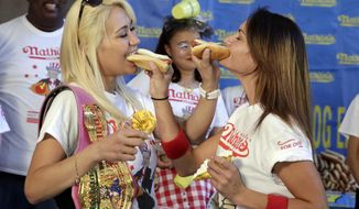 Current women's champion Miki Sudo, left, of Las Vegas, and challenger Michelle Lesco, of Tuscon, Ariz., feed each other a hot dog Monday, July 3, 2017, during the weigh-in for the 2017 Nathan's Hot Dog Eating Contest, in Brooklyn Borough Hall, in New York. Ms. Suto weighed-in at 126 pounds, while Ms. Lesco tipped the scales at 104.5 pounds.(AP Photo/Richard Drew)