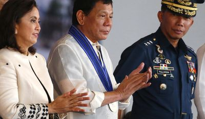 Philippine President Rodrigo Duterte, center,  and Vice President Leni Robredo, left, applaud at the conclusion of the 70th anniversary celebration of the Philippine Air Force at Clark Freeport Zone Tuesday, July 4, 2017 in Pampanga province north of Manila, Philippines. The Philippines' top court on Tuesday upheld President Rodrigo Duterte's martial law declaration in the southern third of the country, dismissing petitions to nullify it.  At right is Air Force Chief Lt.Gen. Edgar Fallorina.(AP Photo/Bullit Marquez)
