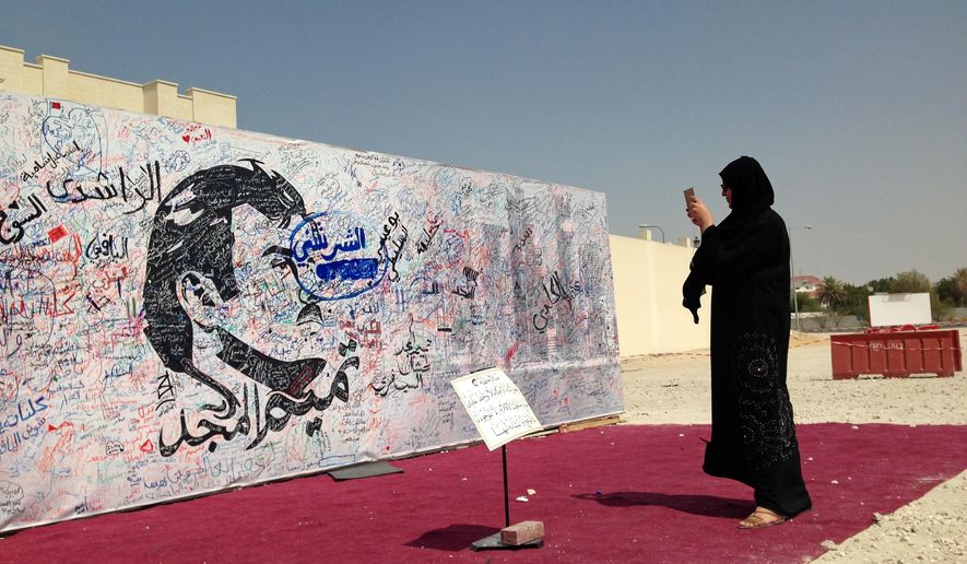 A woman takes a photo of a black-and-white depiction of Qatar's emir, Sheikh Tamim bin Hamad Al Thani, that has attracted signatures and comments of support from residents amid a diplomatic crisis between Qatar and neighboring Arab countries, in Doha, Qatar, Monday, July 3, 2017. A group of Arab nations early on Monday extended a deadline for Qatar to respond to their list of demands in a diplomatic crisis roiling the Gulf by 48 hours, saying Kuwait's emir requested the delay as part of his efforts to mediate the dispute. (AP Photo/Maggie Hyde)