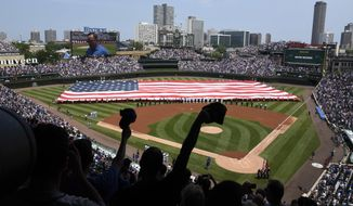 Workers hold an American flag during the singing of the national anthem before a baseball game between the Tampa Bay Rays and the Chicago Cubs on Tuesday, July 4, 2017, in Chicago. (AP Photo/Matt Marton)