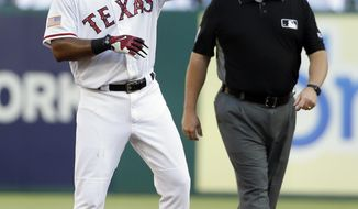 Texas Rangers' Elvis Andrus celebrates hitting a double as second base umpire Bruce Dreckman watches in the first inning of a baseball game, Monday, July 3, 2017, in Arlington, Texas. (AP Photo/Tony Gutierrez)