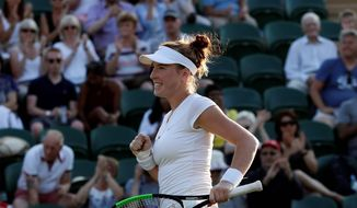 Madison Brengle celebrates after beating two-time Wimbledon champion Petra Kvitova, 6-3,1-6, 6-2, in their women's singles second-round match on Wednesday. (Associated Press)