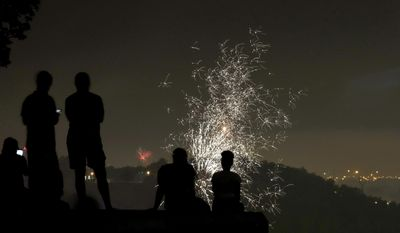 People watch scattered Fourth of July fireworks displays Tuesday, July 4, 2017, from the vantage point of the Liberty Memorial in Kansas City, Mo. (AP Photo/Charlie Riedel)