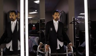 Jamie Nieto, a two-time Olympic high jumper who is recovering from a spinal cord injury he suffered 14 months ago after a mistimed backflip, looks in the mirror while getting his tuxedo fitted ahead of his July wedding, Wednesday, May 31, 2017, in Pasadena, Calif. On good days, Nieto can shuffle 130 steps without a cane or walker. That's an important distance for the two-time Olympic high jumper. By his estimation, 130 paces takes him from the altar to the church door for his wedding on July 22. (AP Photo/Jae C. Hong)