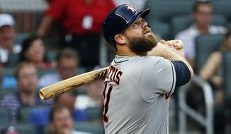 Houston Astros catcher Evan Gattis (11) drives in a run with a base hit in the first inning of a baseball game against the Atlanta Braves Wednesday, July 5, 2017, in Atlanta. (AP Photo/John Bazemore)