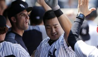 New York Yankees' Ji-Man Choi, center, celebrates with teammates after hitting a fifth-inning, two-run, home run in his first day as a member of the Yankees in a baseball game against the Toronto Blue Jays in New York, Wednesday, July 5, 2017. (AP Photo/Kathy Willens)