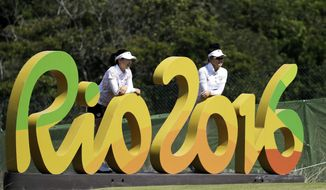 FILE - In this Aug. 16, 2016 file photo, Kelly Tan, left, and Michelle Koh, both of Malaysia, pose for a photo with the Rio 2016 logo on the 16th hole during a practice round for the women's golf event at the 2016 Summer Olympics in Rio de Janeiro, Brazil. Almost a year after the Rio Olympics, Brazilian organizers are asking for help from the International Olympic Committee in order to pay creditors. (AP Photo/Chris Carlson, File)