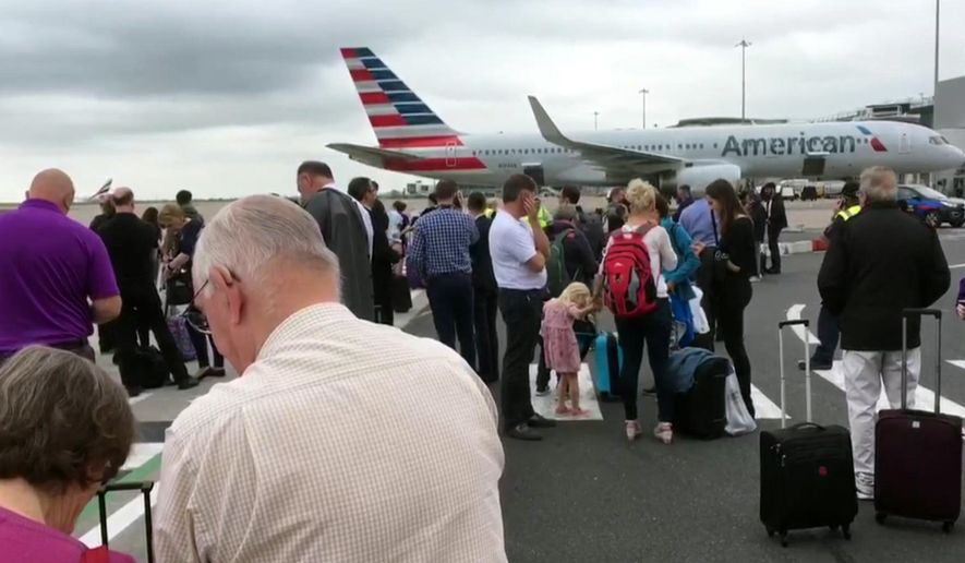 In this image taken from video, passengers stand on the tarmac after being evacuated at Manchester Airport, England, Wednesday July 5, 2017. Manchester Airport says a terminal has been evacuated while authorities investigate a suspicious bag. (AP Photo)