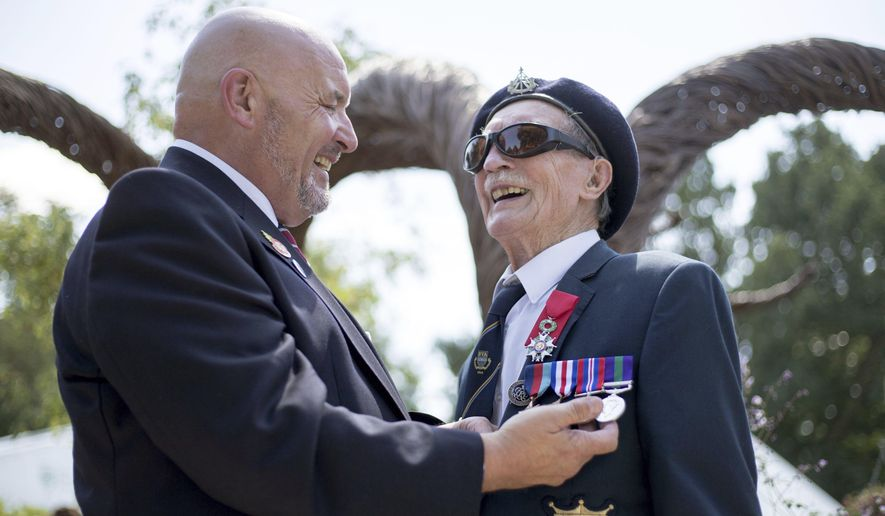 Blind D-Day veteran Alfred Barlow, right, 96, who lost his medals at a motorway service station, is presented with replacements by fellow blind veteran Alan Walker at a ceremony at the Hampton Court Flower Show in south west London, Wednesday, July 5, 2017. Mr Barlow, a blind World War II veteran who participated in the invasion of Normandy, has received a replacement set of medals after losing his own on a pilgrimage to the battlefields in France. (Steve Parsons/PA via AP)