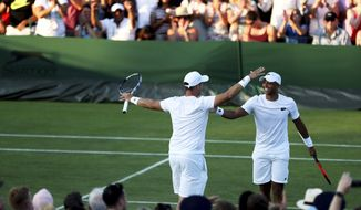 Marcus Willis, left, and Jay Clarke of Britain celebrate winning their doubles match against Jared Donaldson of the US and Jeevan Nedunchezhiyan of India on day three at the Wimbledon Tennis Championships in London, Wednesday, July 5, 2017. (Steven Paston/PA via AP)
