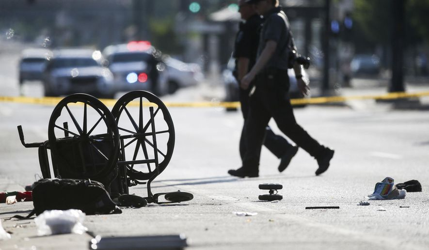 A wheelchair, shoes and other items lay in the street at the scene of an accident at the intersection of 200 South and 400 West Streets in Salt Lake City on Tuesday, July 4, 2017. Police say a car drove onto the sidewalk. (Spenser Heaps/The Deseret News via AP)