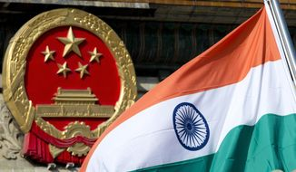 File - In this Wednesday, Oct. 23,2013, file photo, an Indian national flag is flown next to the Chinese national emblem during a welcome ceremony for visiting Indian officals outside the Great Hall of the People in Beijing. China is insisting that India withdraw its troops from a disputed Himalayan plateau before talks can take place to settle the most protracted standoff in recent years between the nuclear-armed neighbors. (AP Photo/Andy Wong, File)