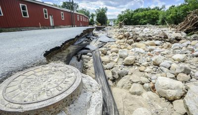 This Monday, July 3, 2017 photo, shows  a washed away portion of Newton Road in Rutland, Vt., during heavy rain on Saturday, July 1. According Daryl Burlett, Director of Brandon Public Works, rocks clogged the Neshobe River up stream, causing it to divert its path across Newton Road. (Robert L. Layman/The Rutland Herald via AP)