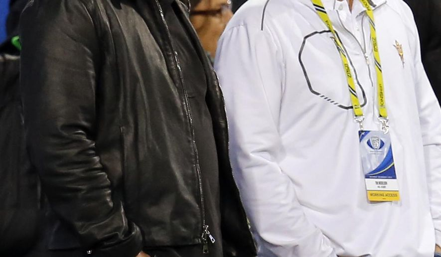 """FILE - In this Dec. 7, 2013, file photo, PGA golfer Phil Mickelson, left, and his brother, Tim Mickelson, watch from the sidelines during the first half of the NCAA Pac-12 Championship football game between Arizona State and Stanford, in Tempe, Ariz. Phil Mickelson heads into the next phase of his career with a new caddie on a course marking its comeback from devastating floods in West Virginia. Mickelson will have brother Tim Mickelson on his bag starting Thursday, July 6, 2017, at the Greenbrier Classic in his first tournament since parting ways with his caddie of 25 years, Jim """"Bones"""" Mackay. (AP Photo/Matt York, File)"""