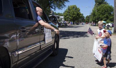 """Flint Bishop Airport police officer Lt. Jeff Neville hands out rubber bracelets from the """"Concern Over Police Safety (C.O.P.S.)"""" truck, pulling a float during the 27th annual Fourth of July Freedom Festival parade honoring Neville in downtown Fenton, Mich., on Tuesday, July 4, 2017. Lt. Neville was stabbed in the neck while on duty last month at the airport. (Shannon Millard /The Flint Journal-MLive.com via AP)"""