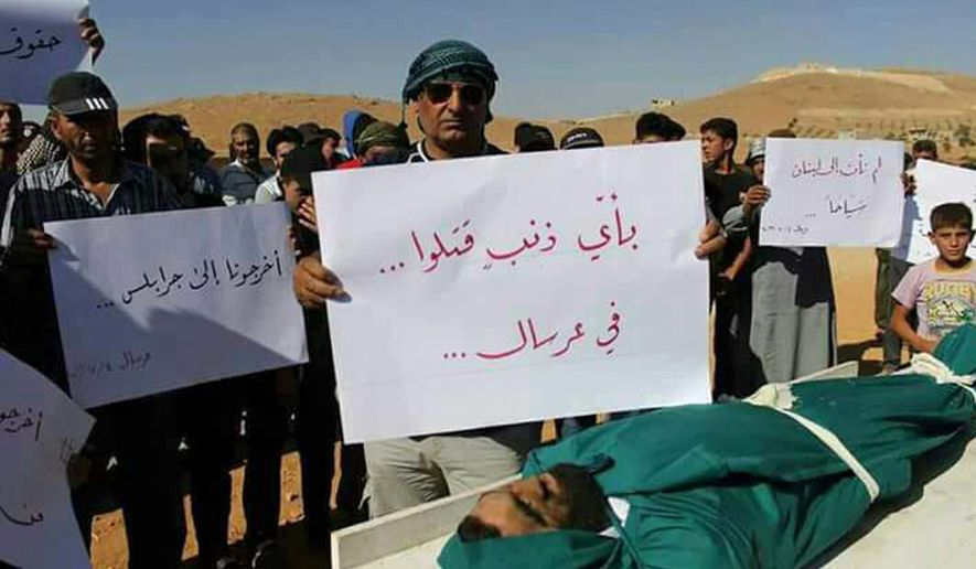 "This Tuesday, July 4, 2017 photo, shows Syrian refugees holding placards as they stand by the body of a deceased Syrian man, in the town of Arsal, near the Syrian border, in northeast Lebanon. Anger mounted among Syrians in Lebanon Wednesday with at least one Syrian opposition group and an international human rights organization calling for a quick investigation after the death of at least four Syrians in Lebanese army custody. The placard in Arabic, center, reads, ""For what crime was he killed? ... In Arsal,"" and at right, ""We haven't come to Lebanon for tourism,"" and left, ""Take us to Jarablus [Syria].""  (AP Photo)"