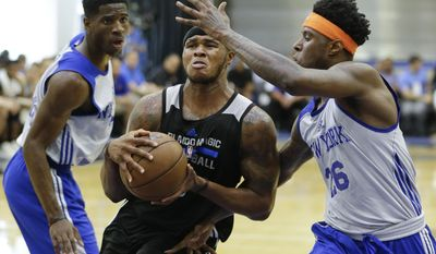 Orlando Magic's Marcus Georges-Hunt, center, drives to the basket between New York Knicks' Damyean Dotson, left, and Jamel Artis (26) during the second half of an NBA summer league basketball game, Wednesday, July 5, 2017, in Orlando, Fla. (AP Photo/John Raoux)