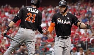 Miami Marlins' Giancarlo Stanton, right, is congratulated by teammate Christian Yelich after hitting a solo home run during the first inning of the team's baseball game against the St. Louis Cardinals on Wednesday, July 5, 2017, in St. Louis. (AP Photo/Jeff Roberson)