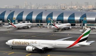 FILE -- In this March 22, 2017 file photo, an Emirates plane taxis to a gate at Dubai International Airport in Dubai, United Arab Emirates. Dubai-based Emirates airlines says the U.S. has exempted it from a ban on laptops in airplane cabins. (AP Photo/Adam Schreck, File)