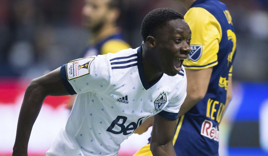 FILE - In this March 2, 2017, file photo, Vancouver Whitecaps' Alphonso Davies, front, celebrates after scoring a goal as New York Red Bulls' Aaron Long looks away during the first half of a CONCACAF Champions League soccer quarterfinal in Vancouver, British Columbia. Davies was born in a Ghanaian refugee camp and immigrated to Canada when he was five. Now the 16-year-old Vancouver Whitecaps midfielder is the youngest national team player in Canada's history approaching the Gold Cup.  (Darryl Dyck/The Canadian Press via AP, File)