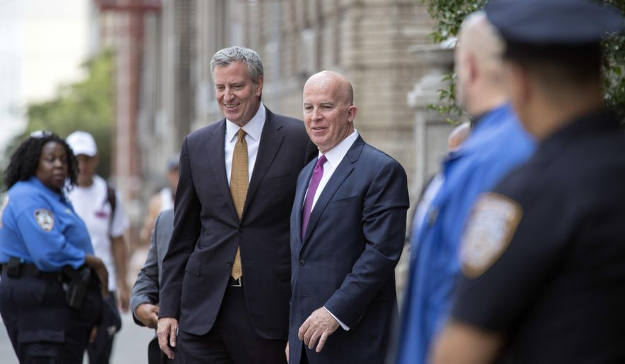 New York Police Dept. Commissioner Jim O'Neil, right, and Mayor Bill de Blasio leave the 46th Precinct after addressing the officers, Wednesday, July 5, 2017 in the Bronx borough of New York. A police officer from the 46th Precinct was shot to death early Wednesday, ambushed inside her command post RV by an ex-convict who once ranted online about his treatment in prison and about police getting away with killing people, authorities said. He was later killed after pulling a gun on police. (AP Photo/Mary Altaffer)