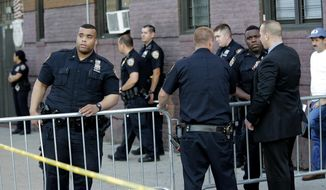 Emergency personnel stand near the scene where a police officer was shot in the Bronx section of New York, Wednesday, July 5, 2017. Police said Officer Miosotis Familia died at a hospital early Wednesday. (AP Photo/Seth Wenig)