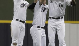 Milwaukee Brewers' Ryan Braun, Hernan Perez and Domingo Santana celebrate after a baseball game against the Baltimore Orioles Wednesday, July 5, 2017, in Milwaukee. The Brewers won 4-0. (AP Photo/Morry Gash)