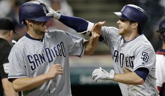 San Diego Padres' Cory Spangenberg, right, grabs Wil Myers's helmet after Spangenberg hit a two-run home run off Cleveland Indians relief pitcher Zach McAllister in the seventh inning of a baseball game, Wednesday, July 5, 2017, in Cleveland. Myers scored on the play. (AP Photo/Tony Dejak)