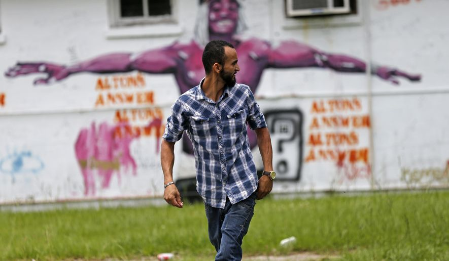 In this June 27, 2017 photo, Abdullah Muflahi walks outside his Triple S Food mart in front of a mural of Alton Sterling in Baton Rouge, La. Little has changed in this poverty-stricken neighborhood since Sterling was shot by police one year ago, a frustrating fact of life for residents and business owners who had hoped a national spotlight on their problems could erode racial tensions and improve police relations in Louisiana's capital. (AP Photo/Gerald Herbert)
