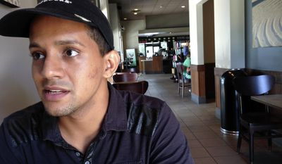 In this Tuesday, June 27, 2017 photo, Carlos Martinez works at a Starbucks store where he is a supervisor in Orlando, Fla. Even though he earned a nursing license in Puerto Rico, Martinez hasn't worked as a nurse since moving to Orlando more than three years ago as he and other professionals from the island are encountering difficulties finding jobs in their chosen fields. (AP Photo/Mike Schneider)