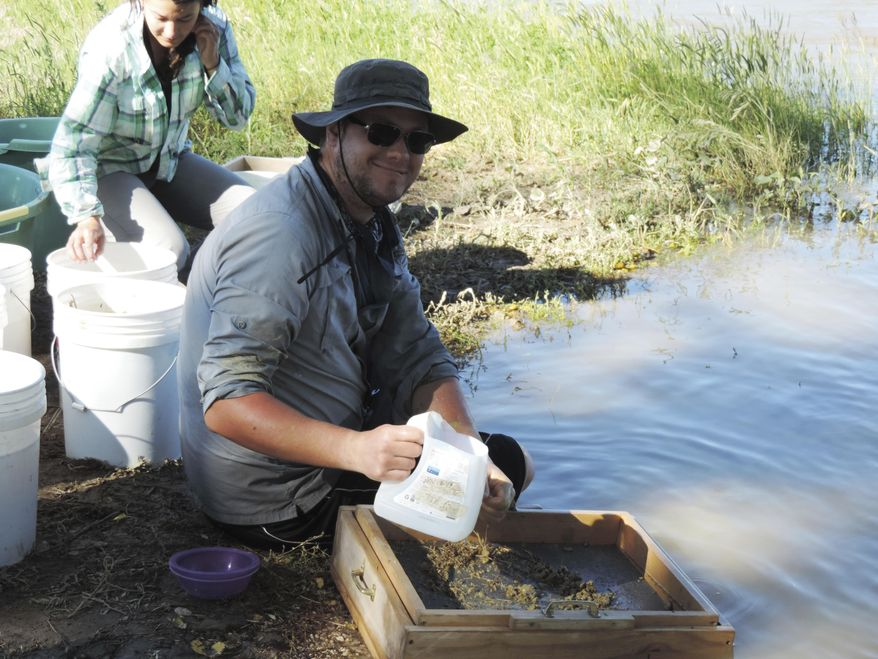 ADVANCE FOR WEDNESDAY JULY 5 AND THEREAFTER - In a June 22, 2017 photo, Lauren Gonzales makes a dirt slurry while David Birlenbach pours an already prepared slurry onto the screens to wash the dirt, in hopes of finding fossils, gathered from an area about 10 miles east of Worland, Wyo., at the Worland Riverside Rotary Park. (Tracie Mitchell/Northern Wyoming Daily News via AP)
