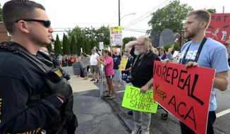 Watched by police, demonstrators against the Senate Republican health care bill await the arrival of Pennsylvania's U.S. Sen. Pat Toomey outside the studios of WHTM-TV, Wednesday, July 5, 2017 in Harrisburg, Pa. Toomey took questions in front of a live audience in public for the first time this year. (AP Photo/Marc Levy)