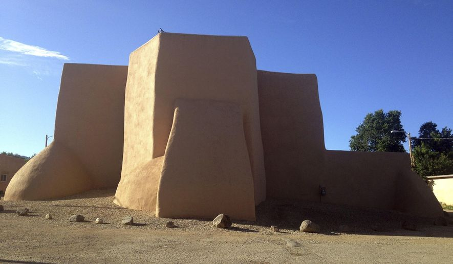 "A July 13, 2015 photo shows the back of San Francisco de Asis Mission Church in Taos, N.M., an image made famous from a Georgia O'Keeffe painting. New Mexico Gov. Susana Martinez unveiled ""record-breaking"" state tourism figures at the Albuquerque International Balloon Museum on Wednesday, July 5, 2017. (AP Photo/Russell Contreras)"