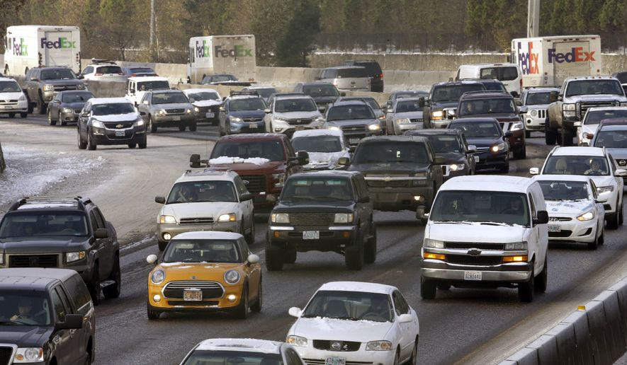 FILE- In this Dec. 16, 2016, file photo cars travel Interstate 5 on the morning commute heading into Portland, Ore. The Oregon House has passed a transportation bill that would raise $3.8 billion in new tax and fee revenue over seven years for repairs to the state's roads and bridges. (AP Photo/Don Ryan, File)