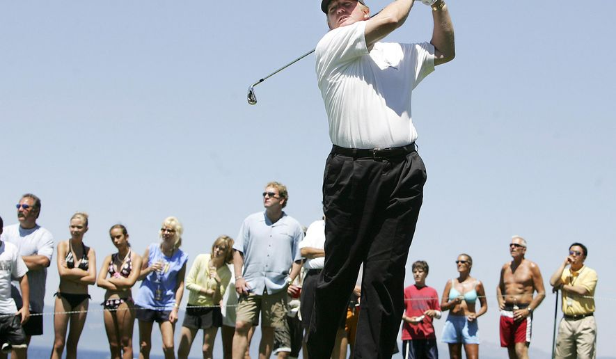 FILE - In this July 17, 2005, file photo, Donald Trump hits off the 17th tee at Edgewood Golf Course during the American Century Championship in Stateline, Nev. A set of golf clubs that Donald Trump gifted to a former caddie before becoming president is being auctioned off. Boston-based RR Auction says Trump used the TaylorMade RAC TP ForgedIrons clubs at the Trump National Golf Club in Bedminster, N.J. (Brad Horn/Nevada Appeal via AP, File)/