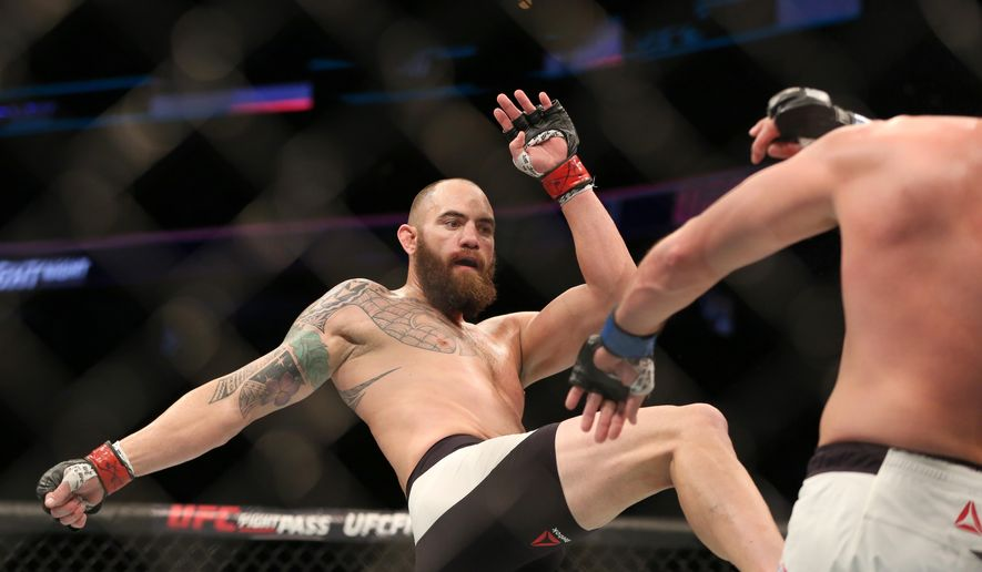 FILE -  In this Jan. 17, 2016, file photo, Travis Browne, left, fights against Matt Mitrione in their mixed martial arts bout at UFC Fight Night 81, in Boston. Travis Browne's relationship with Ronda Rousey blossomed while his mixed martial arts career fell apart with three straight losses. Browne says his fiancee's support is the main reason he's still in the cage and preparing for a crucial fight Saturday at UFC 213. (AP Photo/Gregory Payan, File)