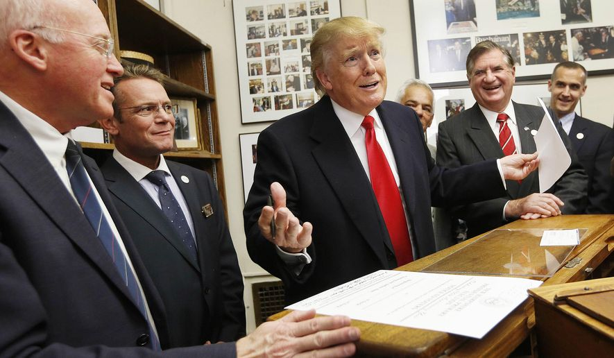 In this Nov. 4, 2015, file photo, New Hampshire Secretary of State Bill Gardner, left, watches at left as Republican presidential candidate Donald Trump reacts after filling out his filing papers to be on the nation's earliest presidential primary ballot at the Secretary of State's office in Concord, N.H. Gardner has been defending the request for detailed voter information from the Trump administration's commission on voter fraud. Gardner, a member of the commission, plans to provide publicly-accessible information, though critics argue state law allows the entire database to be provided only to political parties, political committees and candidates. Gardner is facing criticism for his decision, including from residents who inundated his office with calls. (AP Photo/Jim Cole, File)