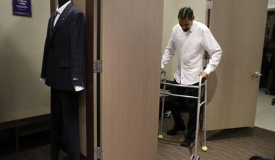 """Jamie Nieto, a two-time Olympic high jumper who is recovering from a spinal cord injury, uses his walker as he steps out of a fitting room while getting his tuxedo fitted ahead of his July wedding, Wednesday, May 31, 2017, in Pasadena, Calif. Nieto was paralyzed last year when he celebrated by doing his trademark backflip during a training session. """"My short-term goal is to walk at our wedding. That's what I'm working towards,"""" said Nieto. (AP Photo/Jae C. Hong)"""