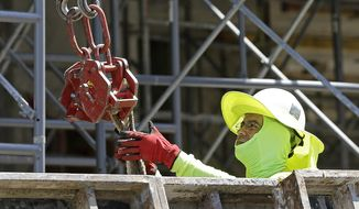 In this Thursday, June 15, 2017, photo, a construction worker continues work on a condominium project in Coral Gables, Fla. On Friday, July 7, 2017, the Labor Department will release the U.S. jobs report for June. (AP Photo/Alan Diaz)